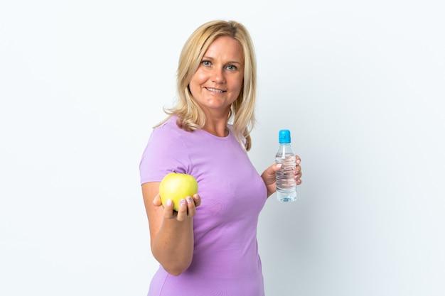 リンゴと水のボトルで白い壁に隔離された中年の女性