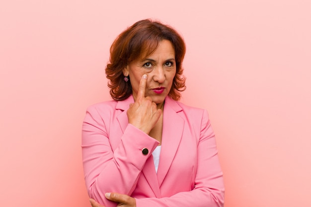 Middle age woman keeping an eye on you, not trusting, watching and staying alert and vigilant against pink wall