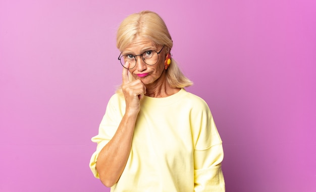 Middle age woman keeping an eye on you, not trusting, watching and staying alert and vigilant
