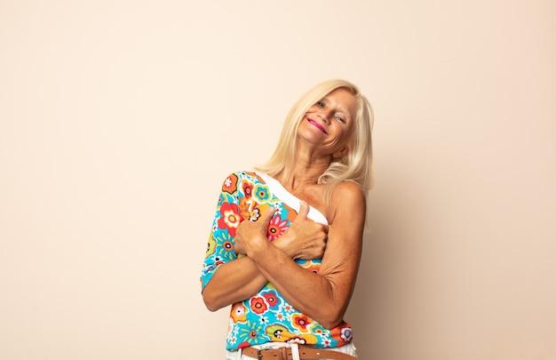 편안하고 긍정적이며 만족스러운 포즈로 팔을 교차시켜 행복하게 웃고있는 중년 여성
