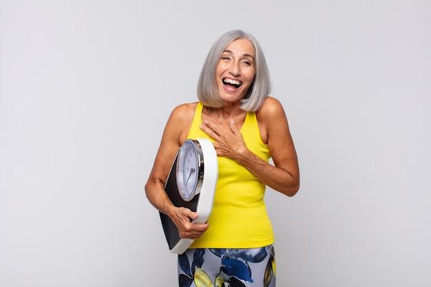 陽気な冗談で大声で笑い、幸せで陽気に感じ、楽しんでいる中年の女性。フィットネスコンセプト