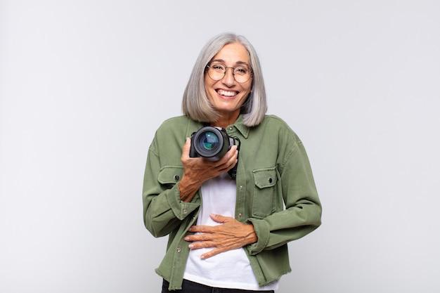 陽気な冗談で大声で笑い、幸せで陽気に感じ、楽しんでいる中年の女性。写真家のコンセプト