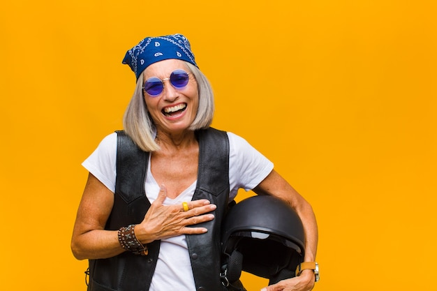 Женщина среднего возраста громко смеется над какой-то веселой шуткой, чувствует себя счастливой и веселой, веселится
