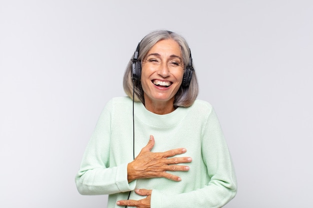 Middle age woman laughing out loud at some hilarious joke, feeling happy and cheerful, having fun. music concept