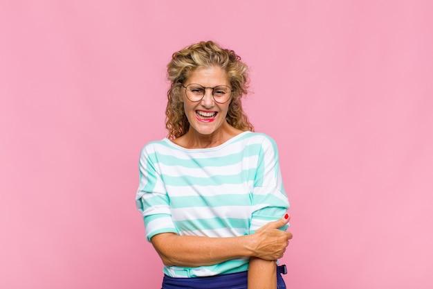 恥ずかしがり屋で元気に笑う中年女性、フレンドリーで前向きだが不安な態度