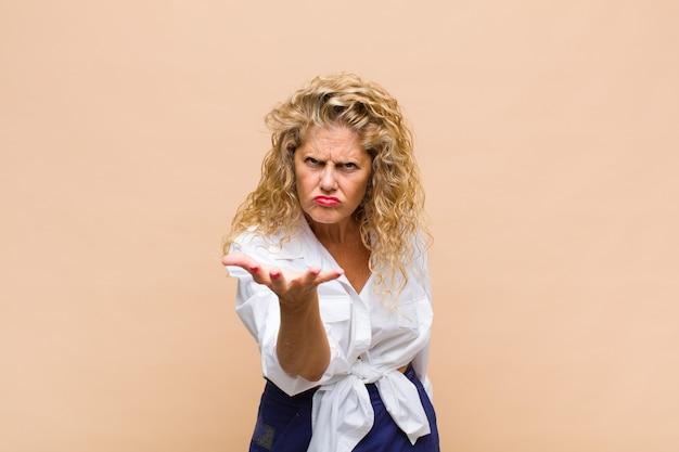 怒っている、イライラしている、欲求不満の叫び声のwtfを探している中年の女性、またはあなたの何が問題なのか