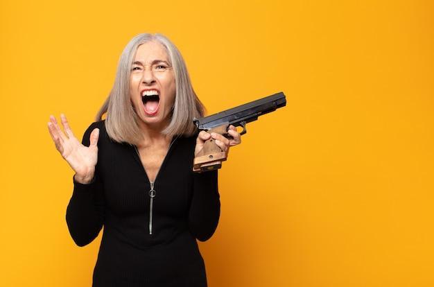 Женщина среднего возраста выглядит сердитой, раздраженной и разочарованной, кричит, черт возьми, или что с тобой не так
