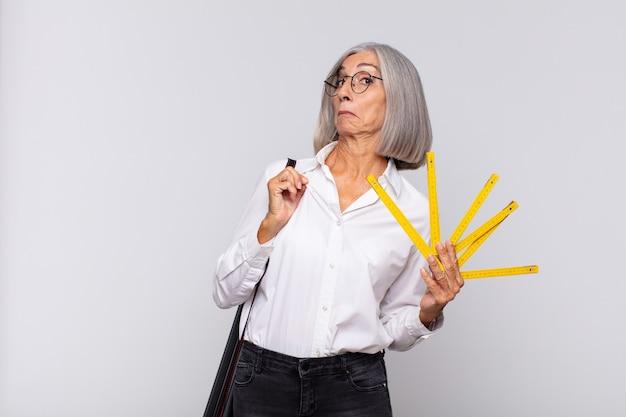 Женщина среднего возраста выглядит высокомерной, успешной, позитивной и гордой, указывая на себя. концепция архитектора
