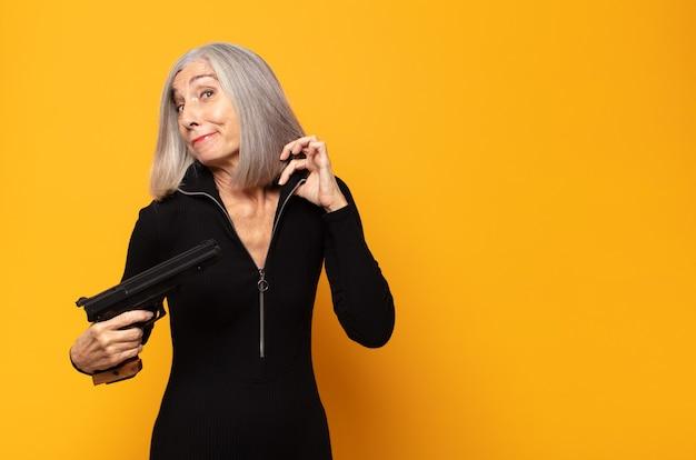 Женщина среднего возраста выглядит высокомерной, успешной, позитивной и гордой, указывая на себя