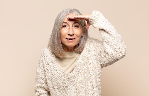 Женщина среднего возраста выглядит сбитой с толку и удивленной, с рукой над лбом смотрит вдаль, смотрит или ищет
