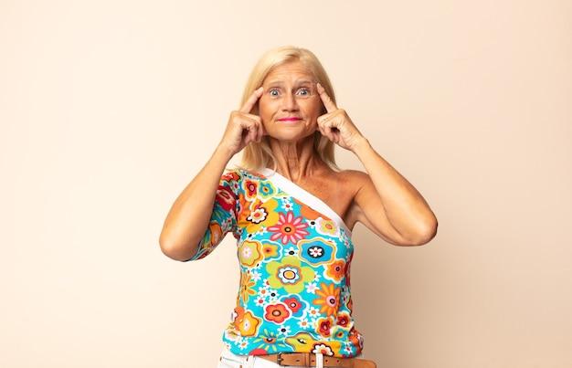 Женщина среднего возраста выглядит сосредоточенной и много думает над идеей, представляя решение проблемы или проблемы