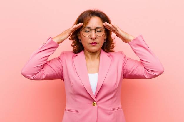 Middle age woman looking concentrated, thoughtful and inspired, brainstorming and imagining with hands on forehead on pink wall