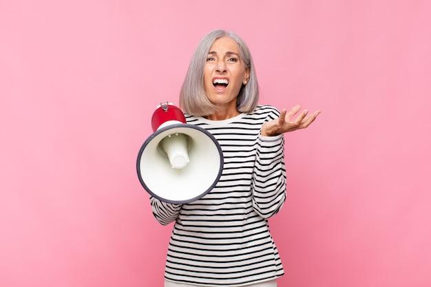 Женщина среднего возраста выглядит отчаянной и разочарованной, напряженной, несчастной и раздраженной, кричит и кричит в мегафон