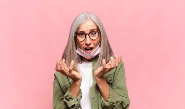 Женщина среднего возраста выглядит отчаявшейся и разочарованной, напряженной, несчастной и раздраженной, кричит и кричит