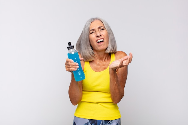 Middle age woman looking desperate and frustrated, stressed, unhappy and annoyed, shouting and screaming. fitness concept