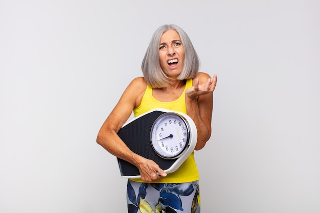 Middle age woman looking desperate and frustrated, stressed, unhappy and annoyed, shouting and screaming