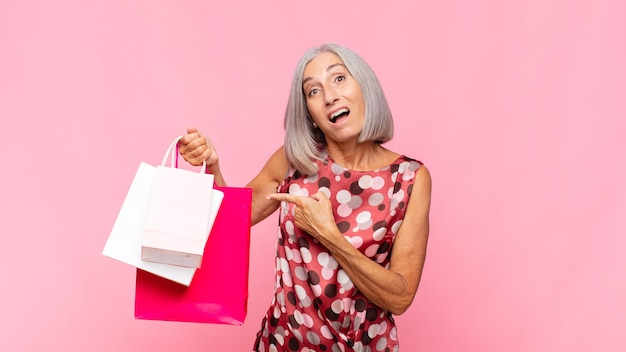 ショッピングバッグでスペースをコピーするために横と上を指して興奮して驚いた中年の女性