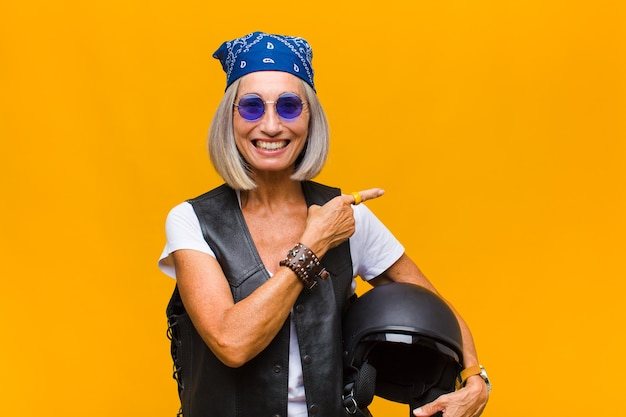 Middle age woman looking excited and surprised pointing to the side and upwards to copy space