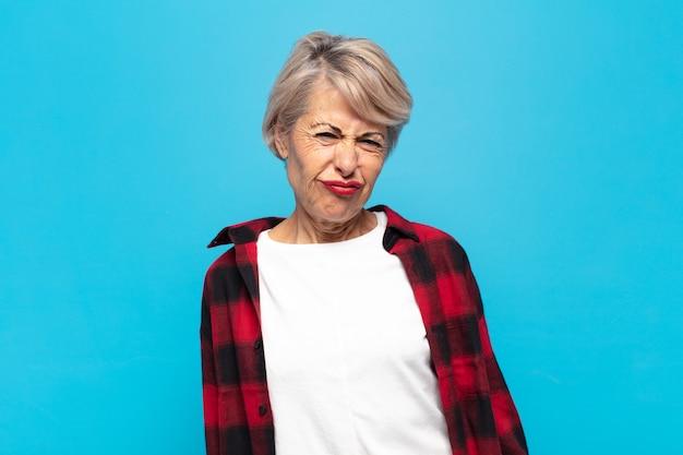 Женщина среднего возраста выглядит глупо и смешно с глупым косоглазым выражением лица, шутит и дурачит