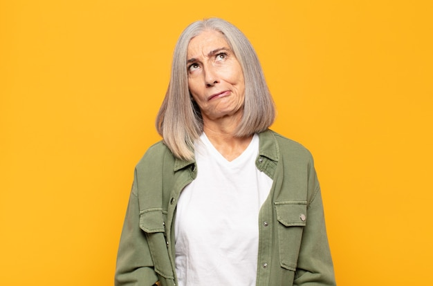 Middle age woman looking goofy and funny with a silly cross-eyed expression, joking and fooling around