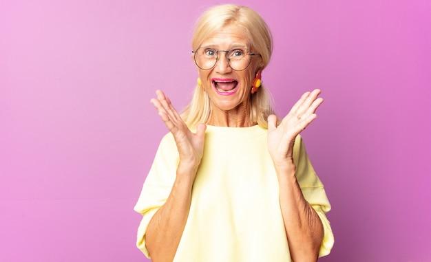 Женщина среднего возраста выглядит счастливой и взволнованной, потрясенной неожиданным сюрпризом, с открытыми руками рядом с лицом
