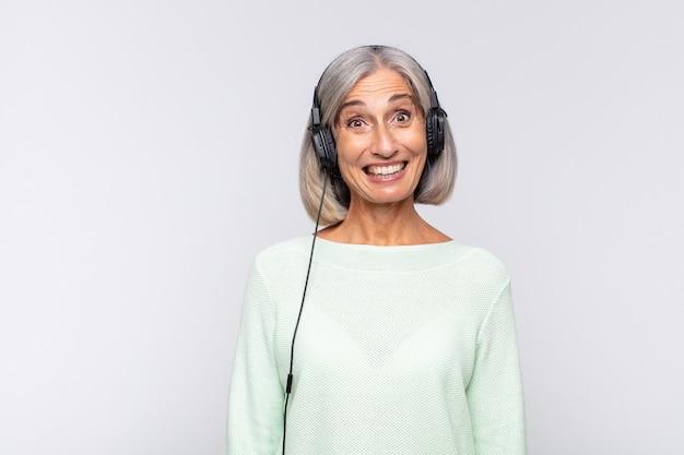 Женщина среднего возраста выглядит счастливой и приятно удивленной, взволнованной, с очарованным и шокированным выражением лица