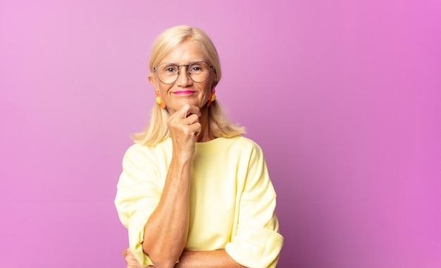 행복하고 턱에 손으로 웃고, 궁금하거나 질문하고, 옵션을 비교하는 중년 여성