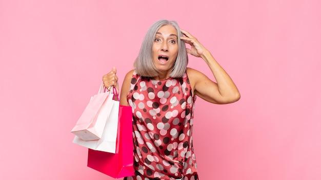 幸せそうに見えて、驚いて、驚いて、笑顔で、買い物袋で驚くべき信じられないほどの良いニュースを実現している中年の女性