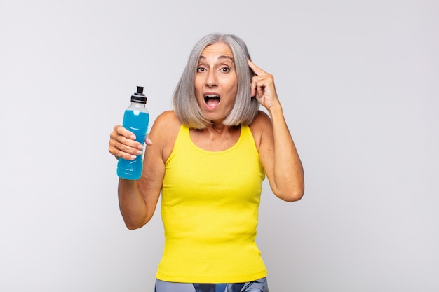 Middle age woman looking happy, astonished and surprised, smiling and realizing amazing and incredible good news. fitness concept