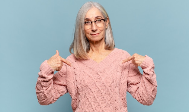 Middle age woman looking proud, positive and casual pointing to chest with both hands