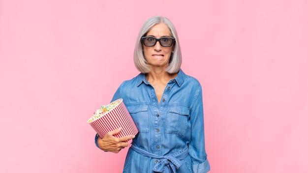 Женщина среднего возраста выглядит озадаченной и сбитой с толку, нервно прикусывает губу, не зная ответа на проблему концепции фильма