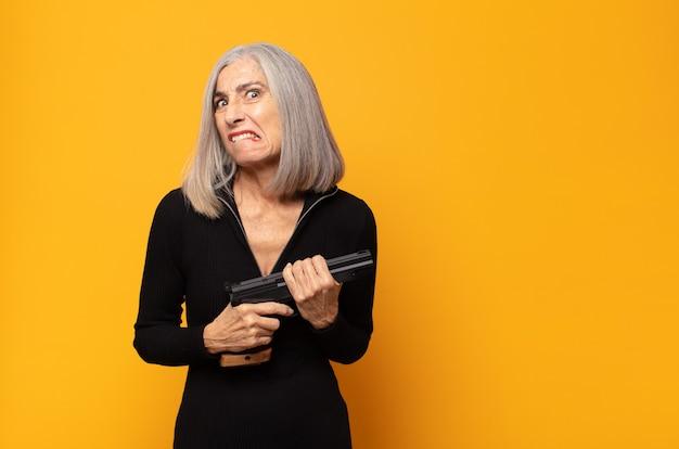 Женщина среднего возраста выглядит озадаченной и сбитой с толку, нервно прикусывает губу, не зная ответа на проблему