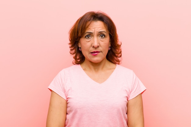 Middle age woman looking puzzled and confused, biting lip with a nervous gesture, not knowing the answer to the problem against pink wall