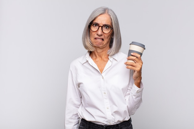 Middle age woman looking puzzled and confused, biting lip with a nervous gesture, not knowing the answer to the problem coffee concept