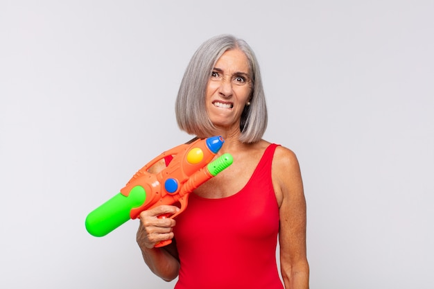 Middle age woman looking puzzled and confused, biting lip with a nervous gesture, not knowing the answer to the problem with a water gun