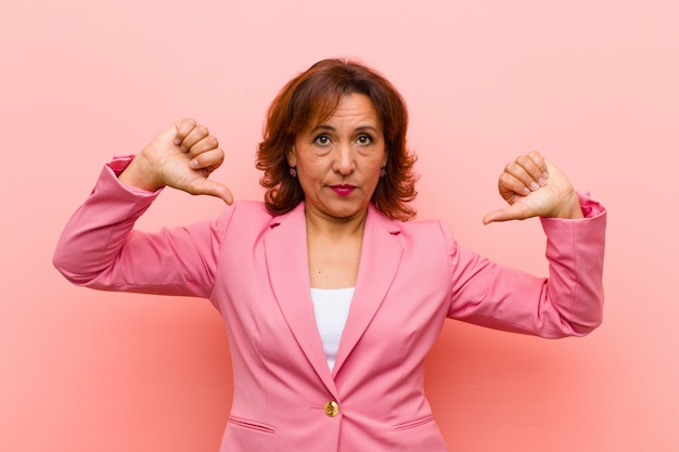 Middle age woman looking sad, disappointed or angry, showing thumbs down in disagreement, feeling frustrated against pink wall