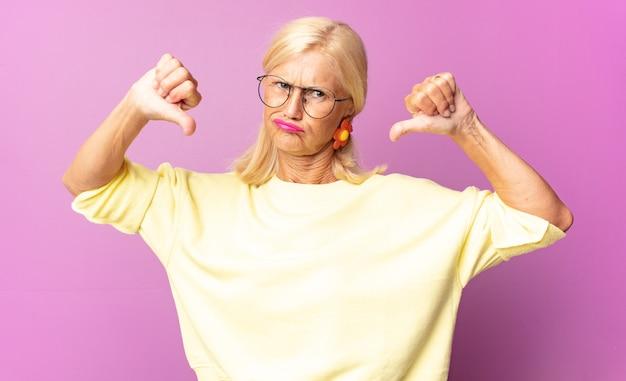 Женщина среднего возраста выглядит грустной, разочарованной или сердитой, показывает палец вниз в знак несогласия, чувствует разочарование