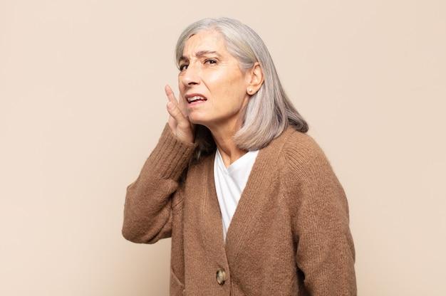 Женщина среднего возраста выглядит серьезной и любопытной, слушает, пытается услышать секретный разговор или сплетню, подслушивает