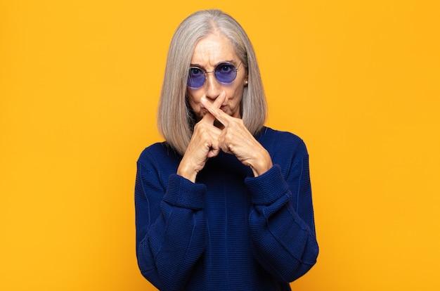 Женщина среднего возраста выглядит серьезной и недовольной, скрестив пальцы в знак отказа, прося молчания