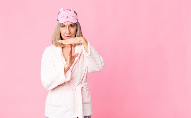Женщина среднего возраста выглядит серьезной, суровой, сердитой и недовольной, делая знак тайм-аута. концепция ночного костюма