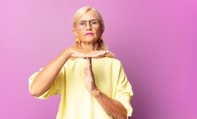 Женщина среднего возраста выглядит серьезной, суровой, сердитой и недовольной, делая знак тайм-аута