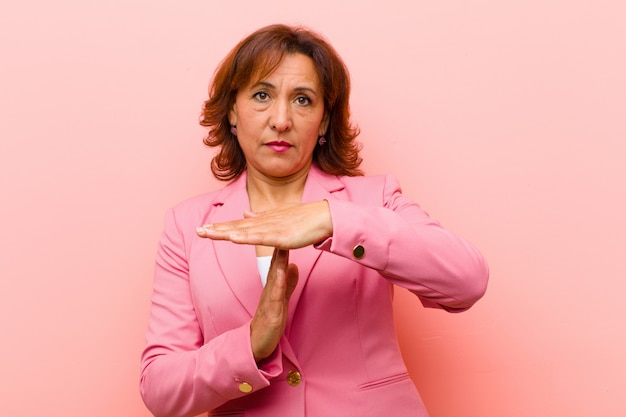 Middle age woman looking serious, stern, angry and displeased, making time out sign  pink wall