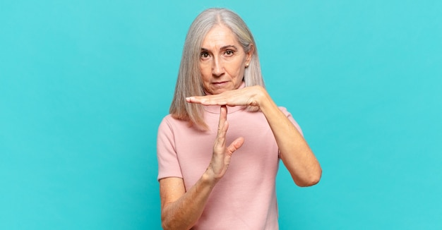 Middle age woman looking serious, stern, angry and displeased, making time out sign