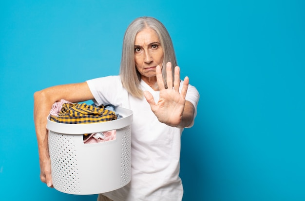Middle age woman looking serious, stern, displeased and angry showing open palm making stop gesture