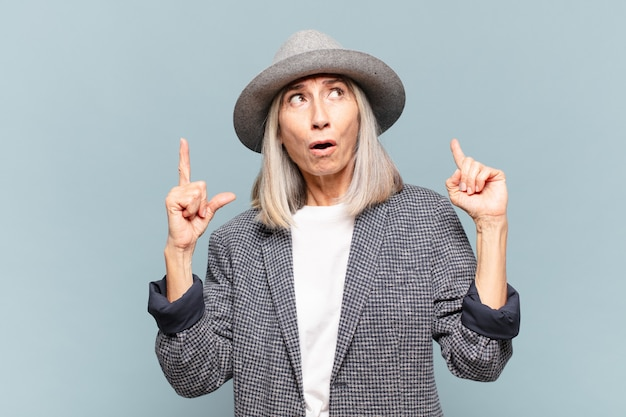 Женщина среднего возраста выглядит потрясенной, изумленной и с открытым ртом, указывая вверх обеими руками, чтобы скопировать пространство