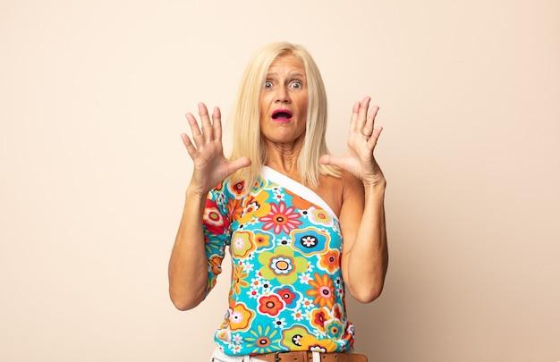 Женщина средних лет выглядит шокированной и удивленной, с удивленной отвисшей челюстью, когда она понимает что-то невероятное