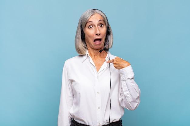 Женщина среднего возраста выглядит шокированной и удивленной с широко открытым ртом