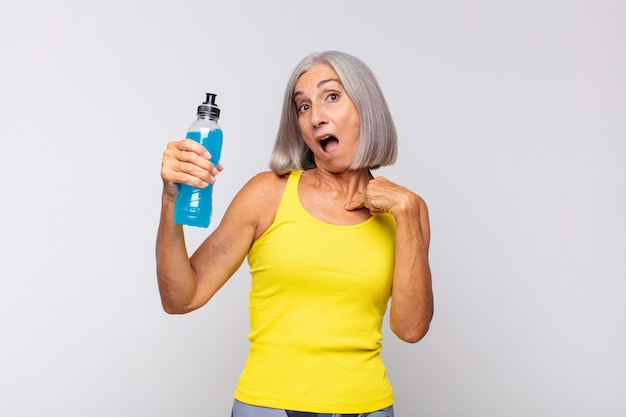 Женщина среднего возраста выглядит шокированной и удивленной с широко открытым ртом, указывая на себя. фитнес-концепция