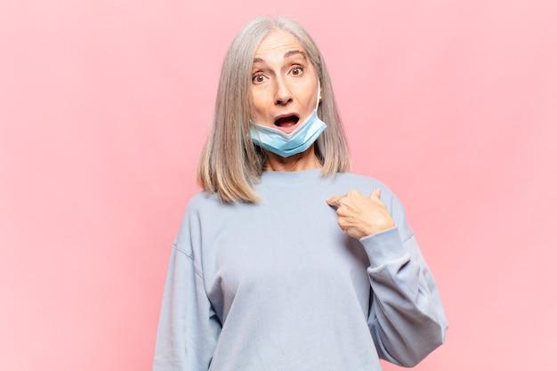 Женщина среднего возраста выглядит шокированной и удивленной с широко открытым ртом, указывая на себя