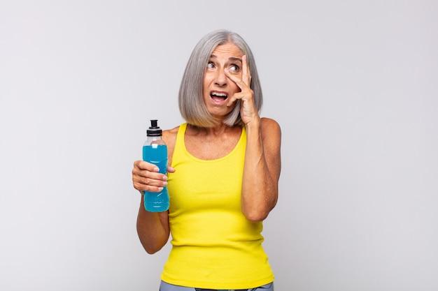중년 여성이 충격을 받거나 무서워하거나 겁에 질려 손으로 얼굴을 가리고 손가락 사이를 들여다보고 있습니다. 피트니스 개념